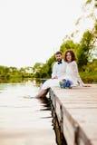 La novia y el novio se están sentando en un embarcadero de madera cerca de la charca Imagenes de archivo