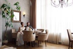 La novia y el novio se sientan en butacas en la tabla en un pasillo brillante hermoso Fotos de archivo libres de regalías