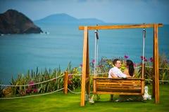 La novia y el novio se sientan en un oscilación fotografía de archivo libre de regalías