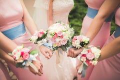 La novia y las damas de honor están mostrando las flores hermosas en sus manos Fotos de archivo