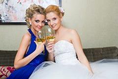 La novia y su dama de honor con un vidrio de vino Foto de archivo libre de regalías