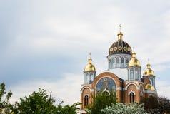 La nueva iglesia ortodoxa con las bóvedas de oro adentro con los árboles florecientes, construye en 1990 el ` s en Kiev, la capit fotos de archivo libres de regalías