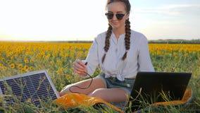 La nueva tecnología, muchacha recarga el ordenador portátil usando la batería solar en el campo de girasoles, aplicación de la mu almacen de video