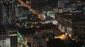 La nuit aérienne a illuminé la vue de paysage urbain des bâtiments modernes de rues de ville de roulement banque de vidéos