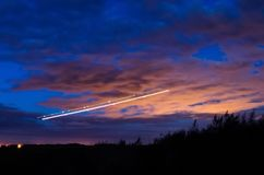 La nuit s'allume, des voies des lumières dans le mouvement des avions sur la longue exposition Photo libre de droits