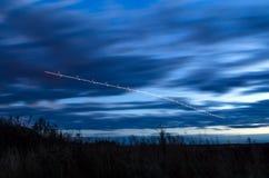 La nuit s'allume, des voies des lumières dans le mouvement des avions sur la longue exposition Images stock