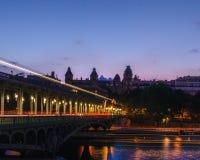 La nuit a tiré du pont BIR-hakeim à Paris avec des lumières dans la longue exposition des tons rouges, oranges et jaunes donnant  image stock