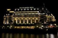 La nuit a tiré du bâtiment d'hôtel de Fullerton dans le bateau de rivière de Singapour Quay Image libre de droits