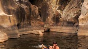 la nuotata della ragazza di aiuti del tipo in lago ha creato tramite la corrente fra le rocce video d archivio