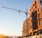 La nuova costruzione di mattone rosso sta costruenda con uso della gru a torre Inverno sparato sul tramonto Concetto della costru Immagini Stock