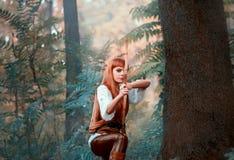 La nuova immagine di Robin Hood come il cacciatore della ragazza, signora attraente in camicia bianca e pantaloni di cuoio ha tir immagini stock libere da diritti