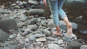 La nuova storia di Robinson Crusoe, una ragazza cammina lungo le pietre fredde sul fiume veloce della montagna, turista perso va  archivi video