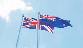 La Nuova Zelanda e la Gran Bretagna, bandiere che ondeggiano contro il cielo blu Immagini Stock