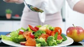 La nutrition appropriée, huile d'olive étant verse sur les légumes, plan rapproché organique frais de salade à la cuisine banque de vidéos