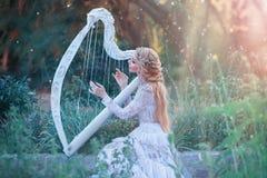 La nymphe mystérieuse de forêt joue sur l'harpe blanche dans l'endroit fabuleux, la fille avec de longs cheveux blonds et la robe image libre de droits