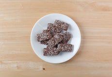 La oblea del chocolate con el coco forma escamas las galletas en una placa blanca Fotografía de archivo