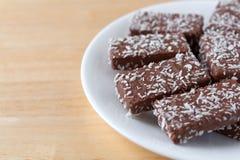 La oblea del chocolate con el coco forma escamas las galletas en una placa blanca Fotos de archivo
