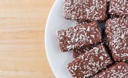 La oblea del chocolate con el coco forma escamas las galletas en una placa blanca Foto de archivo