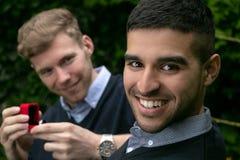 La oferta del compromiso entre dos hombres gay como un hombre propone con un anillo de compromiso en caja roja fotografía de archivo