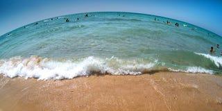 La onda azul en la orilla meridional arenosa en un día de verano caliente encendido Imagenes de archivo