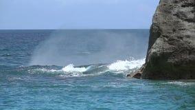 La onda del mar con salpica roturas sobre una roca Cámara lenta metrajes