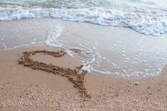 La onda del mar que corre en la playa arenosa está quitando el corazón imagenes de archivo