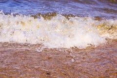 La onda dinámica estalla en la orilla fotografía de archivo