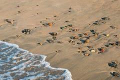 La onda golpea la playa con las piedras coloridas del guijarro - primer fotografía de archivo