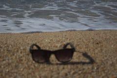 La onda se acerca a las gafas de sol en la playa imagenes de archivo