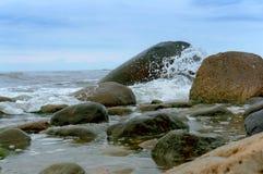 La onda se rompe en las piedras, piedras enormes en la costa imagenes de archivo