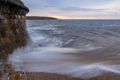 La onda se rompe sobre grada en Filey, North Yorkshire, Reino Unido imagenes de archivo