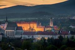 La opinión aérea de la ciudad de la puesta del sol con se enciende para arriba en el krumlov de Cesky Fotografía de archivo
