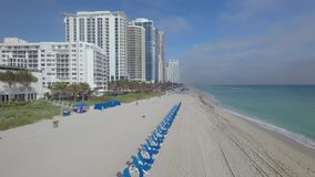 La opinión aérea de la cámara del abejón que sorprende 4k sobre sillas de playa azules de la cubierta en la arena blanca apuntala almacen de metraje de vídeo