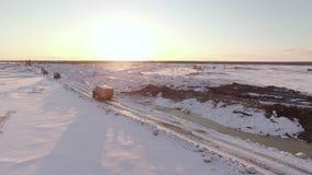 La opinión aérea de la puesta del sol de vehículos convoy la conducción en el camino nevado del invierno almacen de video