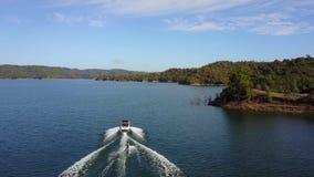 La opinión aérea del abejón hermoso 4k sobre el esquí acuático de la persona ató al barco de motor en paisaje marino tropical del almacen de video