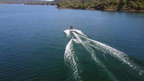 La opinión aérea del abejón maravilloso 4k sobre el esquí acuático de la persona ató al barco de motor en paisaje marino tropical almacen de video
