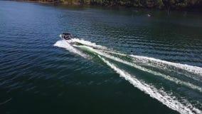 La opinión aérea del abejón que sorprendía 4k sobre el esquí acuático de la persona ató al barco de motor en paisaje marino tropi almacen de video