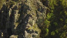 La opinión aérea el escalador libera a solas subir en los acantilados solamente Sirva la subida la roca sin el arnés y cuerdas de almacen de video
