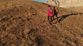 La opinión aérea el viajero de dos muchachas con las mochilas y las cámaras van encima de la colina entre las rocas épicas en las metrajes