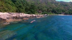 La opinión aérea gente nada en el mar con la máscara cerca de rocas en el día soleado del verano Imagen de archivo libre de regalías