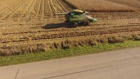 La opinión aérea 4k del abejón sobre cosechadora enorme de la agricultura trabaja a máquina los vehículos de los camiones que cos almacen de metraje de vídeo