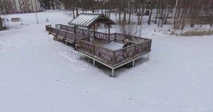 la opinión aérea 4K la mujer joven va abajo y permanece en el muelle de madera cubierto con hielo en el lago congelado en día de  almacen de metraje de vídeo