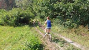 La opinión aérea sobre la muchacha está montando una bici retra en un camino de tierra en un campo cerca del bosque almacen de video