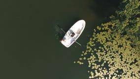 La opinión aérea sobre pares está flotando en un barco en el lago en madera metrajes