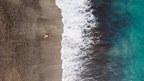 La opinión aérea un hombre en pantalones cortos rojos miente en la playa volcánica negra abandonada en una actitud de la estrella metrajes