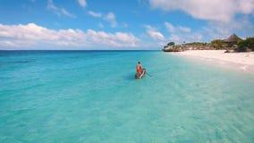 La opinión aérea un pescador de los pobres navega en un bote pequeño a lo largo de una playa tropical almacen de video
