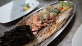 La opinión ascendente cercana el cocinero está acabando el plato delicioso de los mariscos metrajes