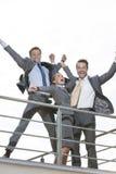 La opinión de ángulo bajo empresarios emocionados con los brazos aumentó la situación en terraza contra el cielo claro Foto de archivo libre de regalías