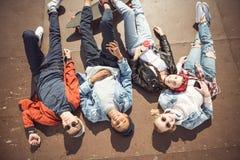 La opinión de alto ángulo adolescentes agrupa la mentira junta y la reclinación Fotografía de archivo