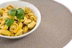 La opinión de alto ángulo de las pastas cocinadas sirvió en cuenco en la estera de lugar Imagenes de archivo